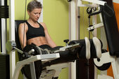 Fitness Woman Exercising Her Legs On Machine — Foto de Stock