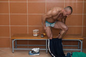 Bodybuilder In Dressing Room - Undressing His Clothing — Stock Photo