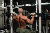 Kulturista dělat cvičení těžké váhy na rameni — Stock fotografie