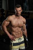 мускулистые юноши, держит вес в руке — Стоковое фото