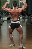 Bodybuilder Performing Rear Double Biceps Pose — Stock Photo