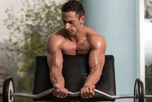 Bodybuilder Performing Biceps Curls With A Barbell — Stock Photo