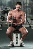 Kulturista cvičení biceps s činkami — Stock fotografie