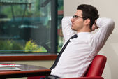 Young Businessman Relaxes Sitting In The Office — Stock Photo