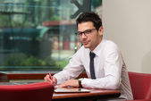 Businessman Sitting At Office Desk Signing A Contract — Foto de Stock
