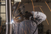 Industrial arc welder working in factory — Stock Photo