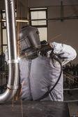 Industrial arc welder working in factory — Stock Photo