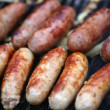 Stock Photo: Lot of grilled sausages close up, barbecue