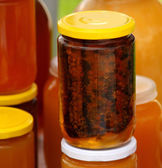 A honeycomb and a honey in a glass jar — Stock Photo