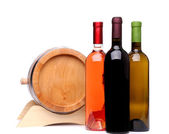 Three wine bottles and wodden barrel — Stock Photo
