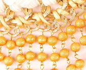Golden pearls with macrame — Stock Photo