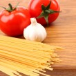 Spaghetti, garlic, tomato, cutting board — Stock Photo #27557045