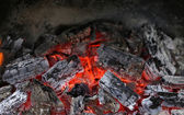Live coals in the oven against black background — Stock Photo