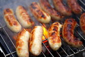 Nicely grilled sausages on a whole background — Stock Photo