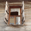 Window of a old wooden house with shutters — Stock Photo