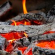 Wooden embers close-up on a whole background — Stock Photo
