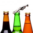 Threee bottles of beer and a opener — Stock Photo