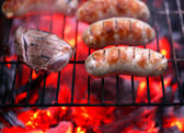 Meat and sausages on BBQ. — Stock Photo