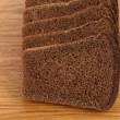 Slices of brown bread on a wooden table. — Stock Photo