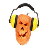 Scary evil face of pumpkin with headphones. — Stock Photo