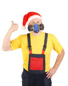 Worker in gas mask and santa hat shows thumb — Stock Photo