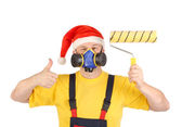 Worker in gas mask and santa hat with roller — Stock Photo