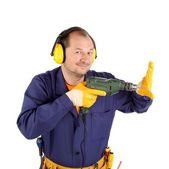 Man in workwear and headphones with a drill — Stok fotoğraf
