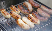 Baking bratwurst sausages on grill. — Stock Photo