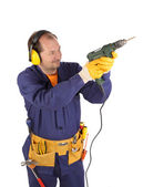Worker in headphones with drill. — Stock fotografie