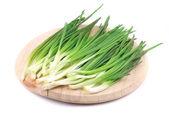 Green onion on wooden platter. — Stock Photo