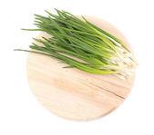 Green onion on wooden platter — Stock Photo
