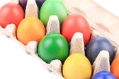 Cardboard egg box with Easter colored eggs — Stock Photo