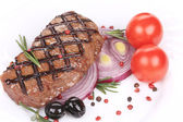 Beef steaks with rosemary and tomatoes. — Stock Photo