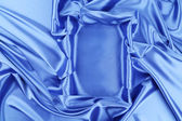 Blue silk soft folds as frame. — Stock Photo