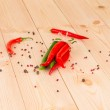 Постер, плакат: Bunch of fresh cayenne red pepper on wood table