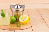 Lemon juicer with juice on wooden background — Stock Photo