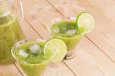 Kiwi smoothie on wooden background — Stock Photo