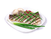Grilled carp fillet on plate with onion. — Stock Photo