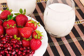 Pomegranate and strawberries with milk. — Stock Photo