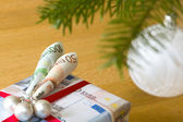 """Gift stylized currency """"Euro"""" under the сhristmas tree — Stock Photo"""