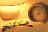 Glasses on the book next to the alarm in the light of a nightlight — Stock Photo