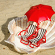 Seashell with miniature deck-chairs — Stock Photo