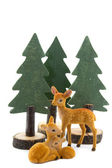Three deer toys with wooden pine trees — Stock Photo