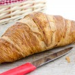 Croissant on a wooden surface — Stock Photo