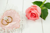 Detail of a cotton heart with wedding rings and rose — Stock Photo