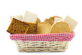 Bread basket filled with slices of bread, crackers, ontbijtkoek — Stock Photo