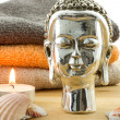Detail of buddha figure with candle, shells and towels — Stock Photo