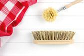 Top-view of dish-washing brush and scrubbing brush and tea towel — Stock Photo