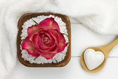 Wooden spoon with heart shaped bath fizzer and bath salt with re — Stock Photo