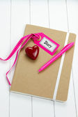 Top-view of diary with pink pen, heart symbol and label tag — Stock Photo